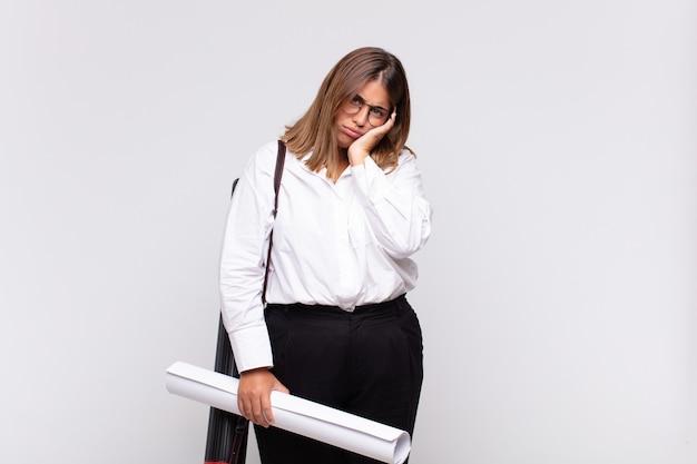 Giovane donna architetto che si sente annoiata, frustrata e assonnata dopo un compito noioso, noioso e noioso, tenendo la faccia con la mano