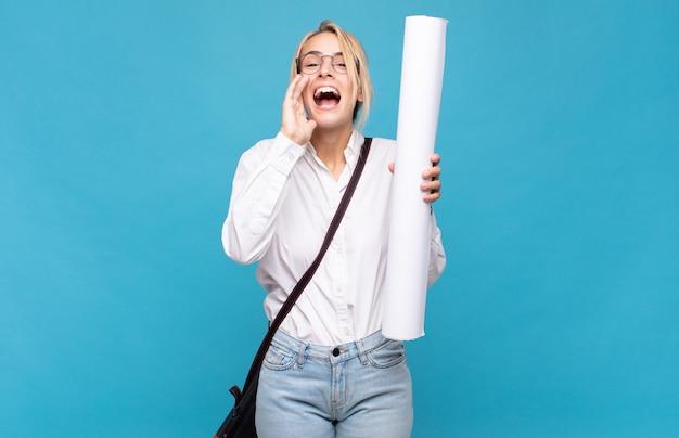 Giovane donna architetto che si sente felice, eccitata e positiva, gridando con le mani vicino alla bocca