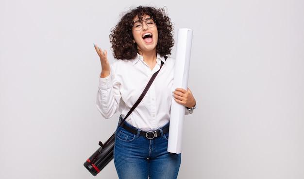 Giovane donna architetto che si sente felice, sorpresa e allegra, sorridente con atteggiamento positivo, realizzando una soluzione o un'idea