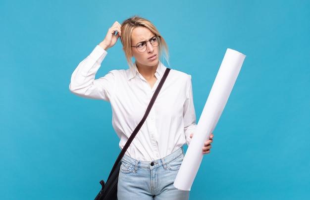 Giovane donna architetto che si sente perplessa e confusa, grattandosi la testa e guardando di lato