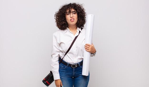 Giovane donna architetto che si sente perplessa e confusa, con un'espressione stupita e sbalordita guardando qualcosa di inaspettato