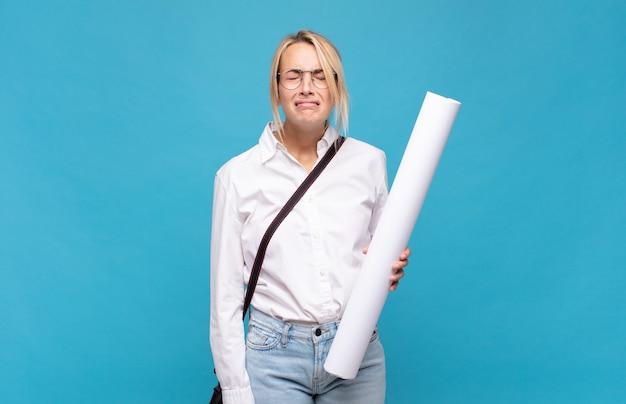 Giovane donna architetto che si sente triste e piagnucolona con uno sguardo infelice, piange con un atteggiamento negativo e frustrato
