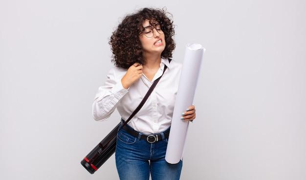 Giovane donna architetto che si sente stressata, ansiosa, stanca e frustrata, tira il collo della camicia, sembra frustrata dal problema