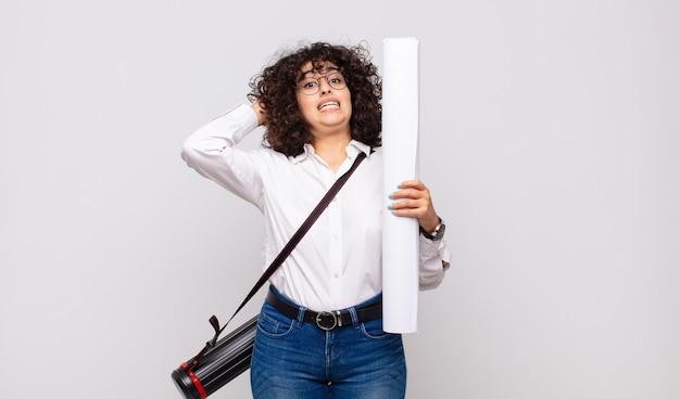 Giovane donna architetto che si sente stressata, preoccupata, ansiosa o spaventata, con le mani sulla testa, in preda al panico per errore