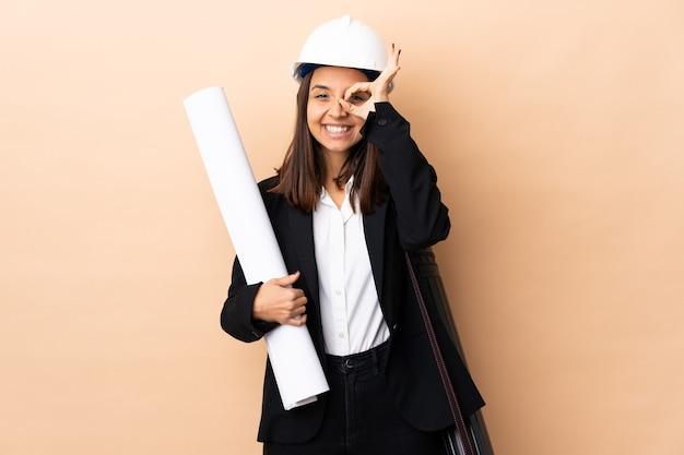 Giovane donna dell'architetto che tiene le cianografie sopra fondo isolato che mostra segno giusto con le dita
