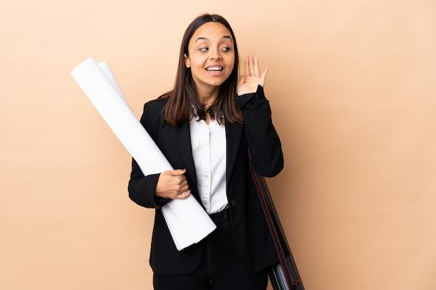 La giovane donna dell'architetto tiene i modelli sopra la parete isolata che ascolta qualcosa mettendo la mano sull'orecchio