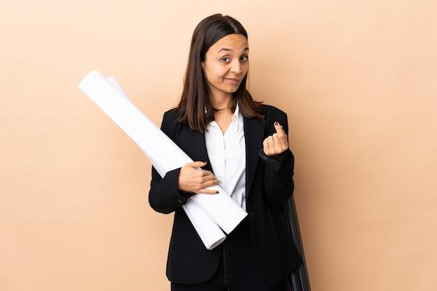 Giovane donna dell'architetto che tiene le cianografie sopra la parete isolata che fa il gesto dei soldi