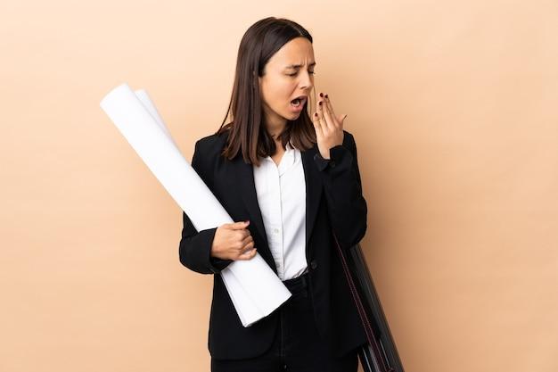 Giovane donna dell'architetto che tiene le cianografie sopra lo sbadiglio isolato e che copre la bocca spalancata con la mano