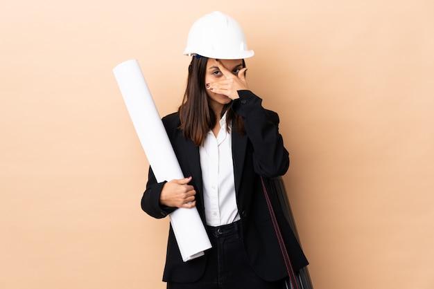 La giovane donna dell'architetto che tiene i modelli sopra il rivestimento della parete osserva a mano e sorridendo