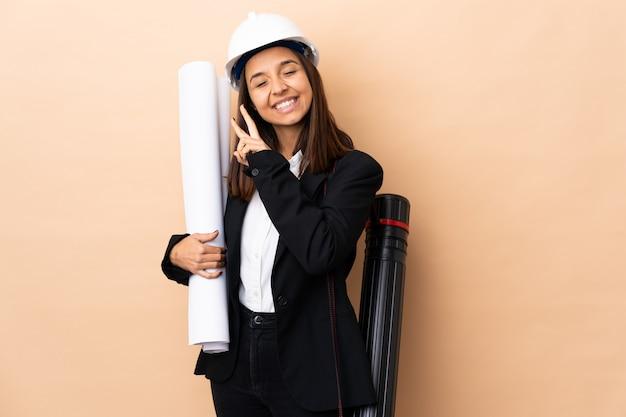 La giovane donna dell'architetto tiene i modelli sopra la parete che sorride e che mostra il segno di vittoria