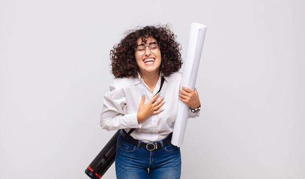 Giovane donna architetto che ride ad alta voce per qualche scherzo esilarante