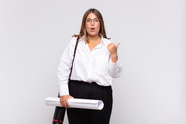 Giovane donna architetto che guarda stupita incredula, indicando un oggetto sul lato e dicendo wow