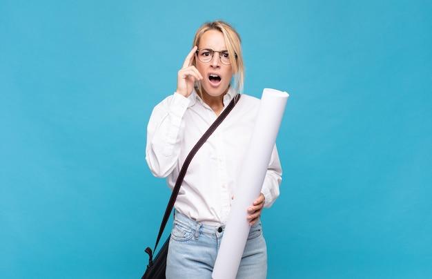 Giovane donna dell'architetto che sembra sorpresa, a bocca aperta, scioccata, realizzando un nuovo pensiero, idea o concetto