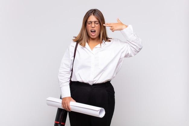 Giovane donna dell'architetto che sembra infelice e stressata, gesto di suicidio che fa il segno della pistola con la mano, indicando la testa
