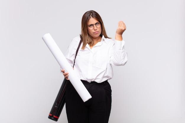 Giovane donna architetto che fa un gesto di capice o denaro, dicendoti di pagare i tuoi debiti!