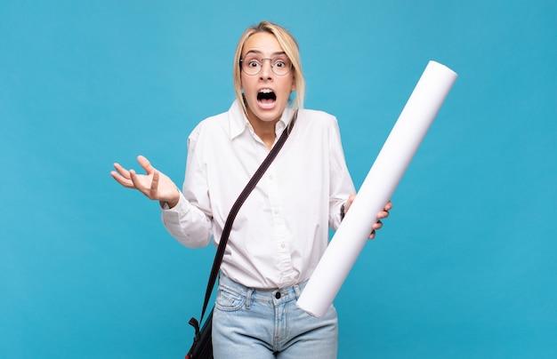 Giovane donna architetto a bocca aperta e stupita, scioccata e sbalordita da un'incredibile sorpresa