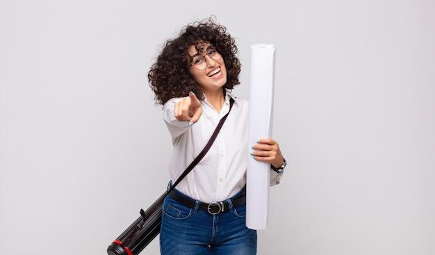 Donna giovane architetto che punta con un sorriso soddisfatto, fiducioso, amichevole, scegliendo te