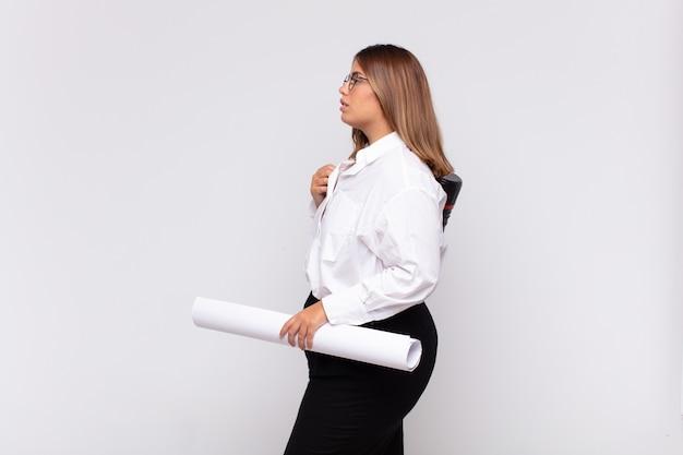 Giovane donna dell'architetto sulla vista di profilo che cerca di copiare lo spazio davanti, pensare, immaginare o fantasticare