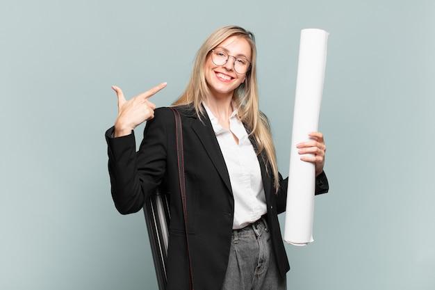 Giovane donna architetto che sorride con sicurezza indicando il proprio ampio sorriso, atteggiamento positivo, rilassato e soddisfatto