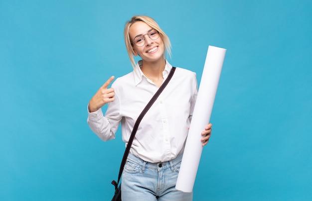 Giovane donna dell'architetto che sorride fiduciosamente indicando il proprio ampio sorriso