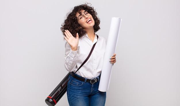 Giovane donna architetto che sorride allegramente e allegramente, agitando la mano, dandoti il benvenuto e salutandoti o salutandoti