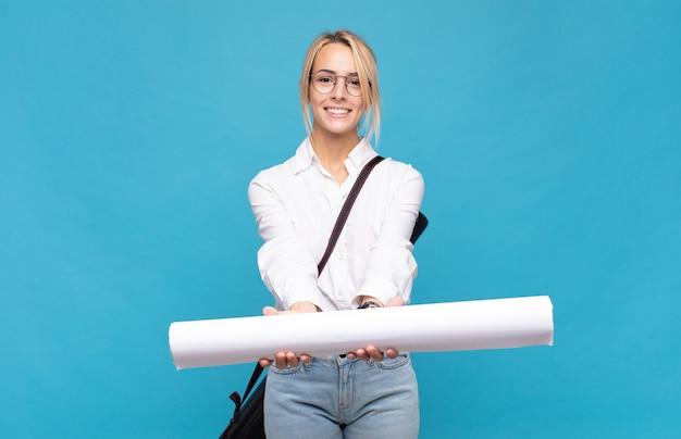 Giovane donna dell'architetto che sorride felicemente con sguardo amichevole, fiducioso, positivo, offrendo e mostrando un oggetto o un concetto