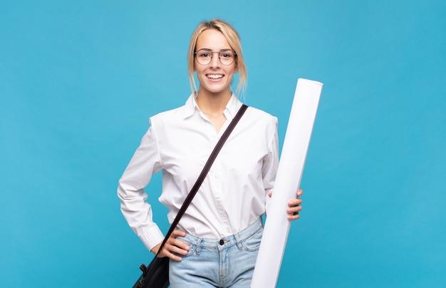 Giovane donna dell'architetto che sorride felicemente con una mano sull'anca e l'atteggiamento fiducioso, positivo, orgoglioso e amichevole