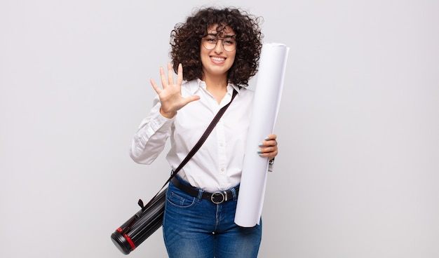 Giovane donna dell'architetto che sorride e che sembra amichevole, mostrando il numero cinque o quinto con la mano in avanti, conto alla rovescia