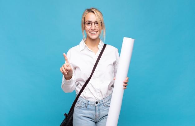 Giovane donna dell'architetto che sorride e che sembra amichevole, mostrando il numero uno o il primo con la mano in avanti, il conto alla rovescia