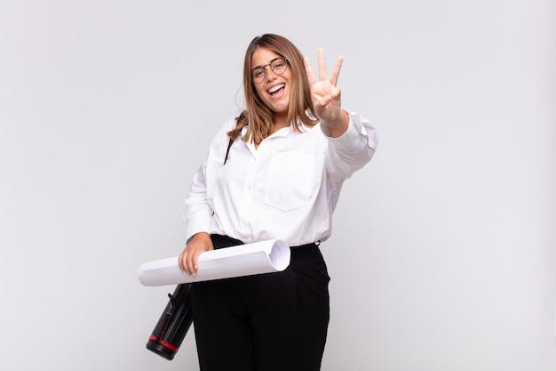 Giovane donna architetto sorridente e guardando amichevole, mostrando il numero tre o terzo con la mano in avanti, conto alla rovescia
