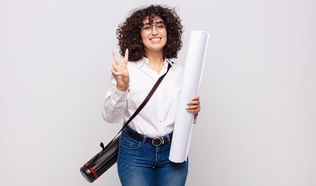 Giovane donna architetto sorridente e guardando amichevole, mostrando il numero due o secondi con la mano in avanti, conto alla rovescia