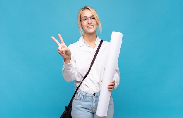 Giovane donna dell'architetto che sorride e che sembra felice, spensierata e positiva, gesticolando vittoria o pace con una mano