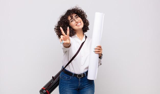 Giovane donna dell'architetto che sorride e sembra felice, spensierata e positiva, gesticolando vittoria o pace con una mano