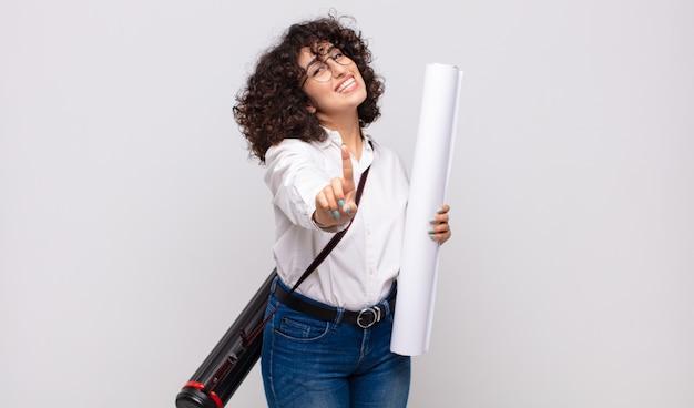 La giovane donna dell'architetto che sorride con orgoglio e sicurezza fa la posa di numero uno trionfante