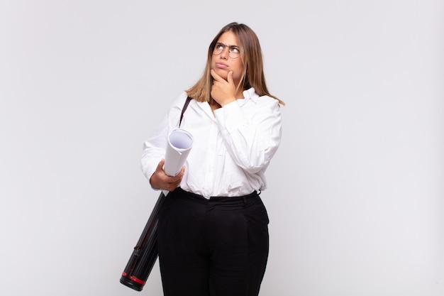 Giovane donna architetto che pensa, si sente dubbiosa e confusa, con diverse opzioni, chiedendosi quale decisione prendere