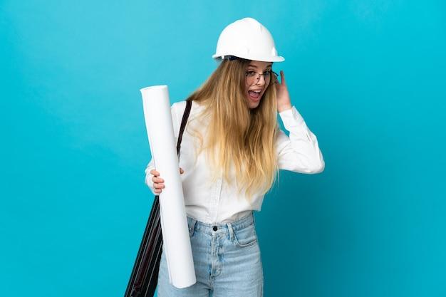 Giovane donna dell'architetto con il casco e che tiene le cianografie sull'azzurro che ascolta qualcosa mettendo la mano sull'orecchio