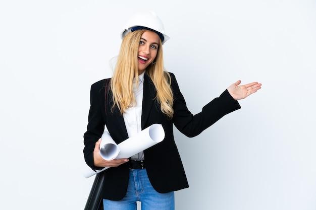 Giovane donna dell'architetto con il casco e che tiene le cianografie sopra il bianco isolato che estende le mani a lato per invitare a venire
