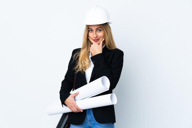 Giovane donna dell'architetto con il casco e che tiene i modelli sopra la risata bianca isolata