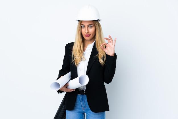 Giovane donna dell'architetto con il casco e la tenuta dei modelli sopra bianco isolato che mostra un segno giusto con le dita