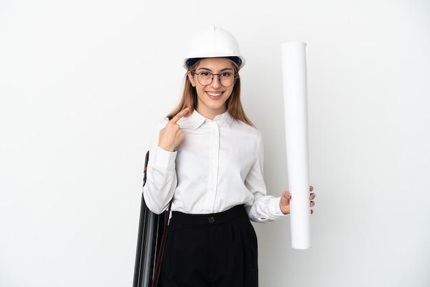 La giovane donna dell'architetto con il casco e che tiene le cianografie isolate sulla parete bianca che dà un pollice aumenta il gesto