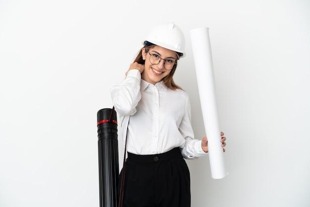Giovane donna dell'architetto con il casco e che tiene le cianografie isolate sulla risata bianca della parete