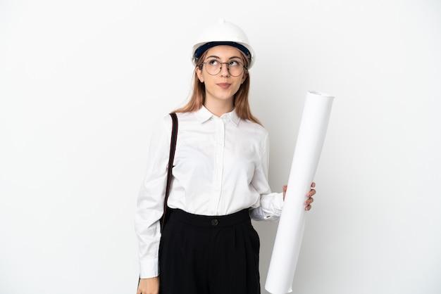 Giovane donna dell'architetto con il casco e che tiene i modelli isolati sul muro bianco e che osserva in su