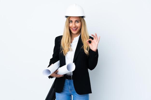 Giovane donna dell'architetto con il casco e la tenuta dei modelli sopra la parete bianca isolata che mostra un segno giusto con le dita
