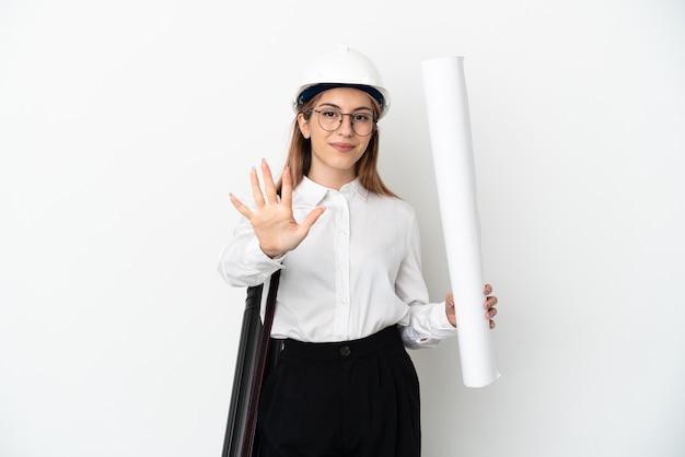 Giovane donna dell'architetto con il casco e che tiene le cianografie su bianco che conta cinque con le dita