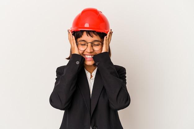 La giovane donna dell'architetto con il casco rosso isolato su fondo bianco ride con gioia tenendo le mani sulla testa. concetto di felicità.