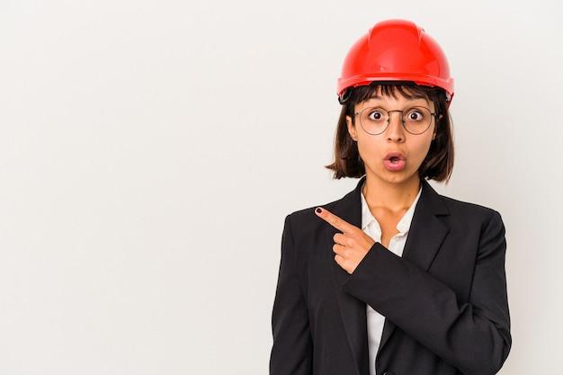 Giovane donna dell'architetto con il casco rosso isolato su fondo bianco che indica il side