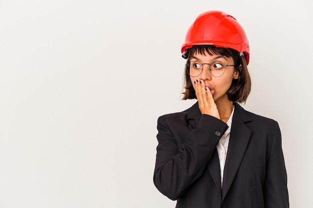Giovane donna architetto con casco rosso isolato su sfondo bianco premuroso guardando uno spazio copia che copre la bocca con la mano.