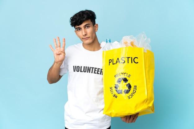 Giovane argentino che tiene una borsa piena di plastica felice e che conta quattro con le dita