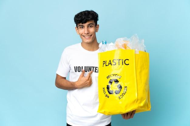 Giovane uomo argentino che tiene un sacchetto pieno di plastica con l'espressione facciale di sorpresa