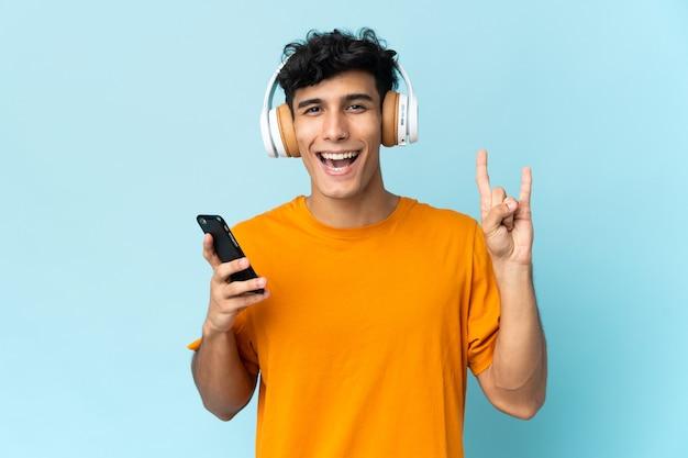 Giovane uomo argentino isolato sulla musica d'ascolto della parete con un gesto di roccia che fa mobile